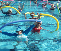 Adults gathered in pool around instructor